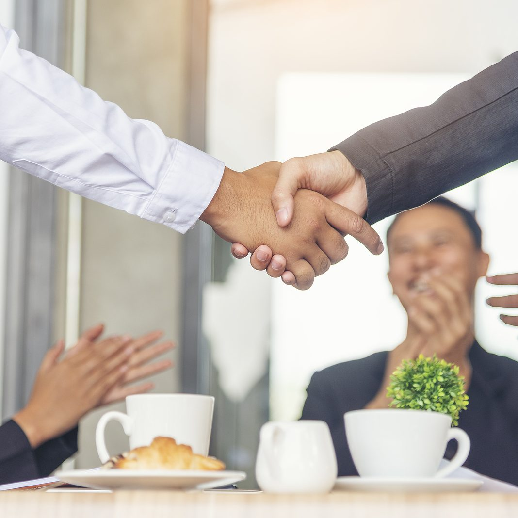 Team Business Partners shaking hands together to Greeting Start up small business in meeting room. Shakehand teamwork partners at modern office handshake together. Business mergers and acquisitions